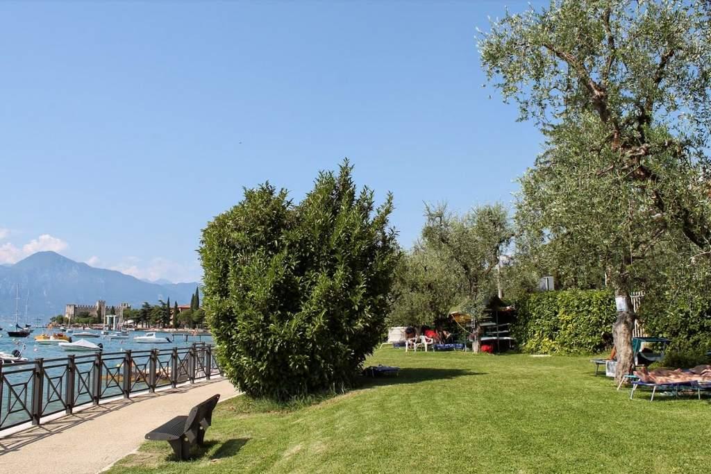 Vista del giardino direttamente sul lago del Camping Olivetisul